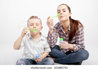 A boy and a woman sit cross-legged on the floor and let go soap bubbles.