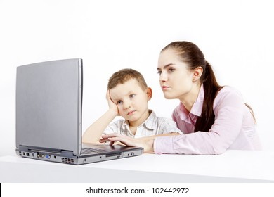 Boy and woman sit at the laptop. He learns use the laptop. She shows and explaines him what to do.