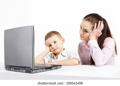 A boy and a woman sitting in front of a laptop. Watching something intently, carefully.