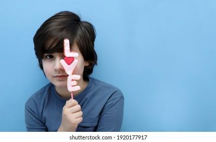 Junge mit dem Wort Liebe durch Marshmallows, der ein Auge bedeckt