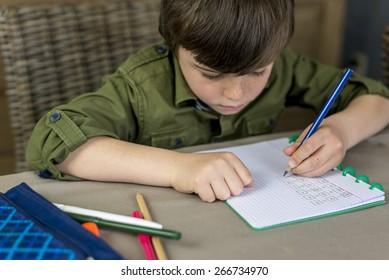 boy working hard on his homework, shallow depth of field