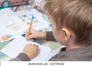 A boy writes English words by hand on traditional white paper in a notebook. The boy writes his first test on English. Child writing, spelling and education. Boy learns english. English writing skills