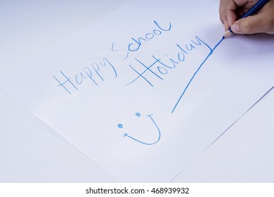 """Boy writing """"HAPPY SCHOOL HOLIDAY"""" on white paper."""
