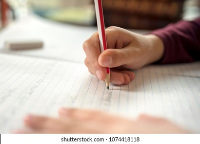 Boy writing in a notepad doing his school work spelling or homework
