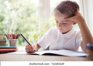 Boy writing in a notepad doing his school work or homework