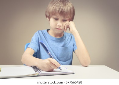 Boy writing on paper notebook. Boy doing his homework exercises. School, education, homeschooling concept