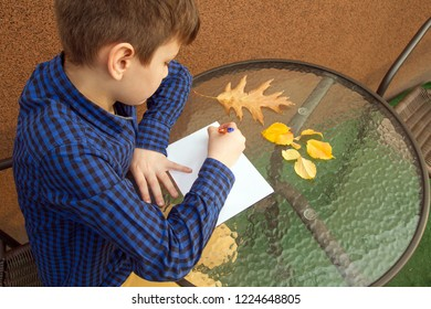Boy is writing something. Boy is doing homework outdoors. Boy is drawing on paper or writing a letter