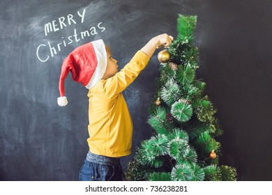 The boy wrote an inscription Merry Cristmas. Christmas tree. Xmas child and New Year holiday Merry Christmas your family