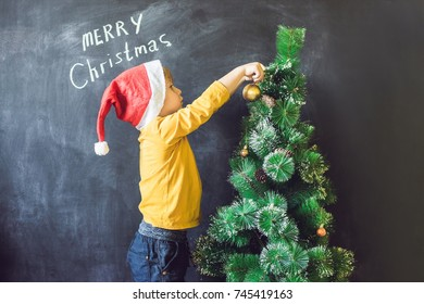 The boy wrote an inscription Merry Cristmas. Christmas tree. Xmas child and New Year holiday Merry Cristmas your family