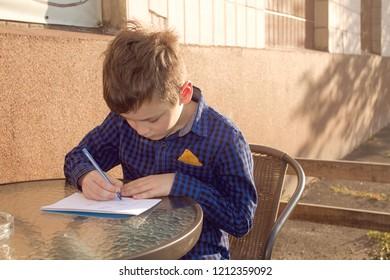 Boy wrtitting something. Boy doing homework outdoors. Boy drawing on paper or wrtitting a letter