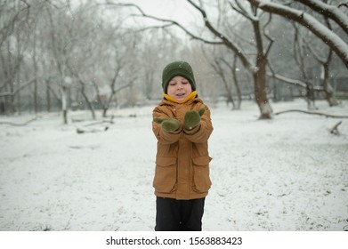 boy in a yellow down jacket and green hat catches snowflakes in his hands from the sky on a winter day