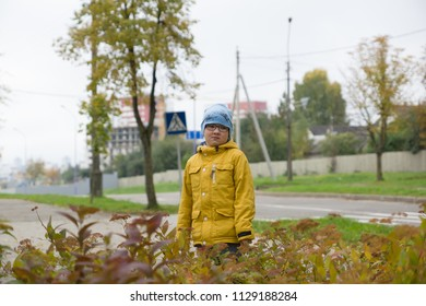 boy in a yellow jacket is resting in an autumn park