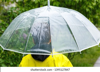 Boy in yellow raincoat holds transparent Umbrella during the rain. Rainy weather at spring, summer