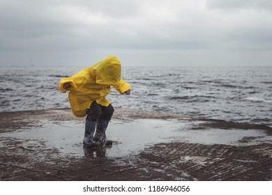 A boy in a yellow raincoat jumps on puddles on the beach.