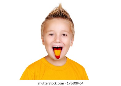 boy in yellow shirt with spanish  flag on his tongue