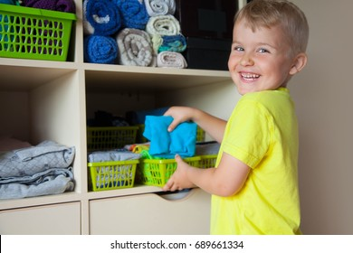 A boy in a yellow T-shirt puts things in a closet by the Mari Kondo system.