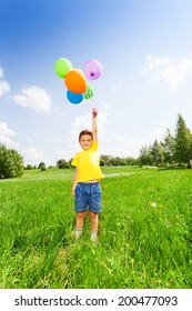 Boy in yellow T-shirt standing with balloons