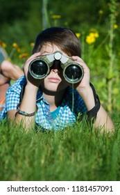 Boy young researcher exploring with binoculars environment in green garden