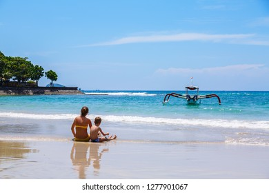A boy and a young woman is sitting on the Candidasa beach, Candi