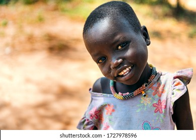 BOYA TRIBE, SOUTH SUDAN - MARCH 10, 2020: Small girl in colorful dress and traditional necklace smiling at camera against blurred rural environment in South Sudan in sunny day