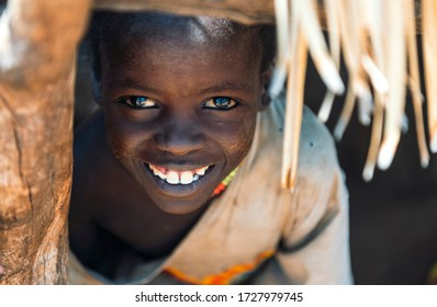 BOYA TRIBE, SOUTH SUDAN - MARCH 10, 2020: Boy with beautiful brown eyes with reflection wearing rags looking out window hole and smiling at camera while hiding at home in village in South Sudan.