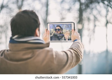 boyfriend chatting to his long distance girlfriend using a tablet outdoors on a sunny winter day. a couple talking over a video call, by using a tablet.