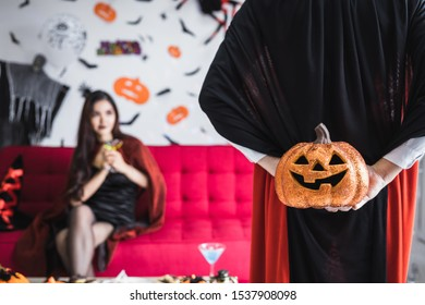 Boyfriend in the Dracula costume surprised his girlfriend by holding an orange Halloween pumpkin behind, with a girlfriend background that was anticipating the gift he received from her boyfriend.