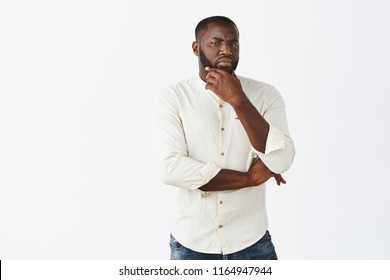 Boyfriend gets suspicious. Portrait of intense African American handsome man with beard staring doubtful and with disbelief at camera, frowning holding hand on jaw, suspecting someone telling lie