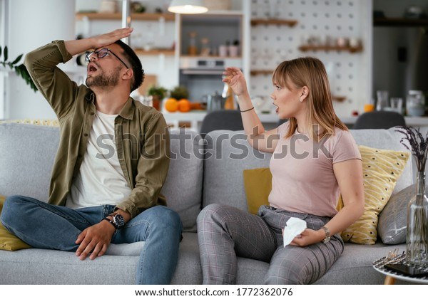 Boyfriend and girlfriend are arguing on the couch. Angry girlfriend is yelling at her boyfriend..