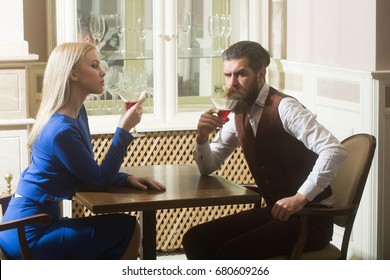 Boyfriend and girlfriend dating in restaurant. Man and woman drinking wine from martini glasses. Couple in love. Alcohol, appetizer, addictive and convive. Unhealthy lifestyle. Bad habits