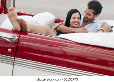 boyfriend and girlfriend lying inside vintage convertible car and hugging. Horizontal shape, full length, side view