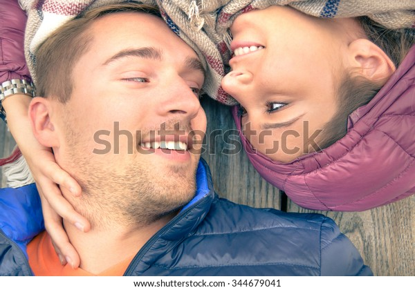 Boyfriend and girlfriend lying taking selfie outdoors with happy face expression looking each other in eyes. Couple of lovers at the beginning of love story having fun together. Vintage filtered look.
