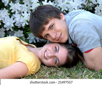 Boyfriend and girlfriend poses cheek to cheek.  Girl is wearing yellow and boy is wearing grey.  Both are smiling.