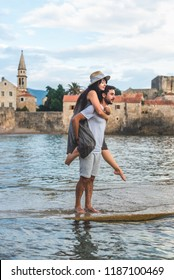 boyfriend giving piggyback to girlfriend on Ricardova Glava beach in Budva, Montenegro