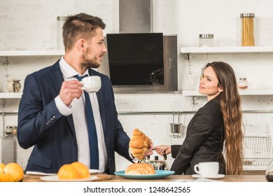 boyfriend having breakfast and girlfriend putting kettle on stove at home, sexism concept