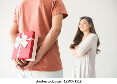boyfriend hold and hide surprise valentine gift box to his beauty Chinese Asian girlfriend with copy space for text.