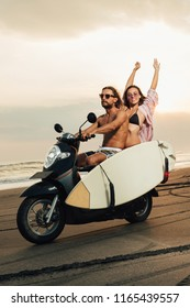 boyfriend riding scooter with surfboard on beach, girlfriend sitting with raised hands
