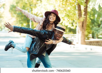 boyfriend in straw hat giving piggyback to his girlfriend while walking in the park
