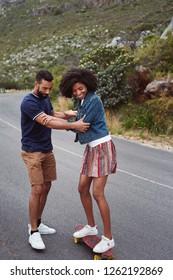 Boyfriend teaching girlfriend how to skateboard, beautiful fun playful couple moment