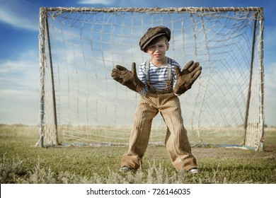 Boy-goalkeeper stands on the gate waiting for the ball