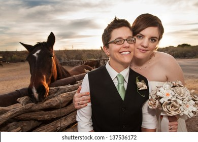 Boyish groom and lesbian bride outdoors near horse