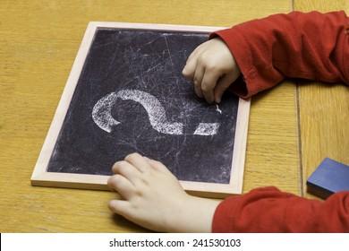 Boys arm drawing question mark on chalk board easel