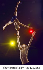Boys athlete acrobats perform acrobatic figures in the arena