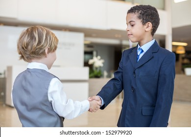 Boys in business clothes shake hands in a business center