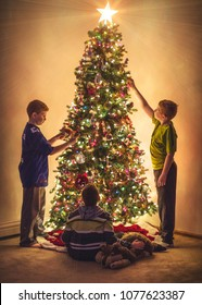 Boys decorating a Christmas tree with vintage style effect