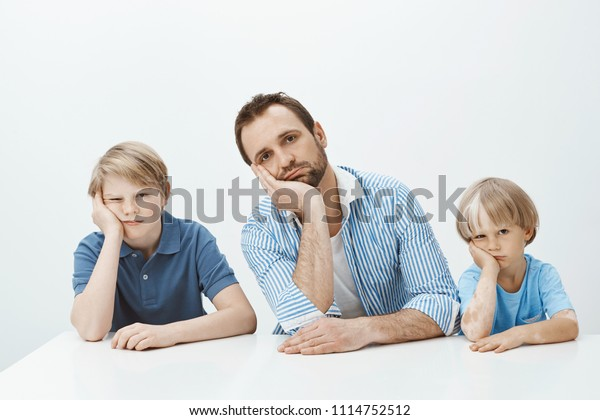 Boys feeling bored and upset. Portrait of tired funny european family of sons and dad sitting at table, leaning heads on palms and staring indifferent at camera, being careless while mom scolding them