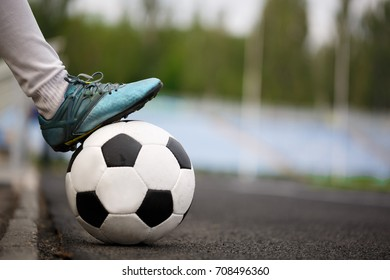 A boy's feet on a soccer ball on an asphalted path background. A round black and white football ball at the stadium. Sports, hobbies, activities concept. Outdoors activities. Copy space.