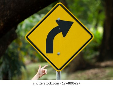 Boy's finger pointing through yellow right turn sign