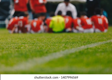 Boys With Football Coach Having Pep Talk Before Youth Sports Tournament Competition. Blurred Horizontal Football Background