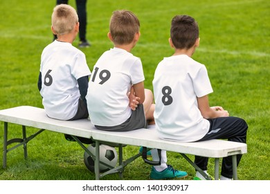 Boys in football team sitting on substitute bench